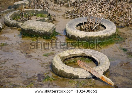 Debris in the form of old car tires and scrap metal in nature - stock photo