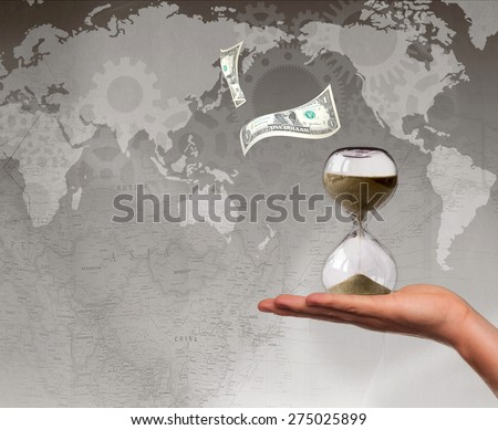 Debt deadline concept. Human hand holding hourglass. US dollars and world map in the background. Space for text  - stock photo
