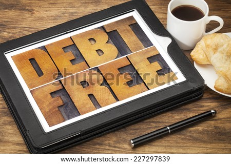 debt free concept - text in vintage letterpress wood type on a digital tablet with coffee and pastry - stock photo