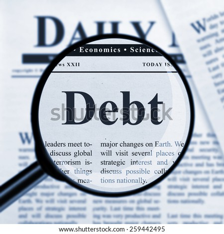 Debt under magnifying glass - stock photo