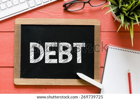 Debt word Handwritten on blackboard. Debt word Handwritten with chalk on blackboard, keyboard,notebook,glasses and green plant on wooden background - stock photo