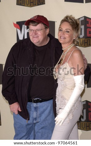 Dec 1, 2004; Los Angeles, CA: Actress SHARON STONE with documentary filmmaker MICHAEL MOORE at the VH1 Big in '04 Awards at the Shrine Auditorium, Los Angeles.  He won the Big Boat Rocker award. - stock photo