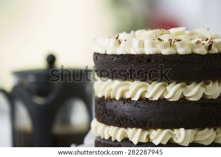 Decadent Chocolate Layer Cake Decorated with White Cream Icing and Coffee Bodum in Background - stock photo