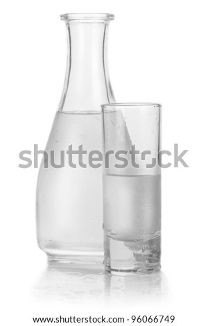 Decanter and glass of iced vodka with drops on white background - stock photo