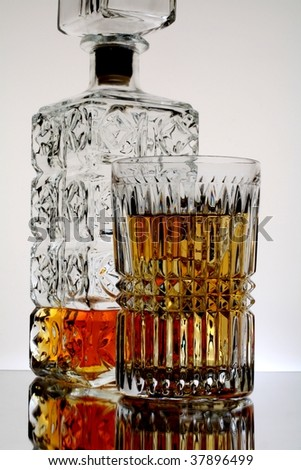Decanter and glass of whiskey and ice against white background. - stock photo