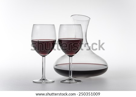 Decanter and two glasses of red wine on white background  - stock photo