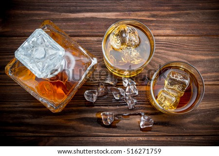 Decanter and two glasses with ice and whiskey on wooden background