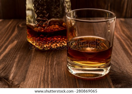 Decanter of whiskey and a glass on a wooden table. Angle view