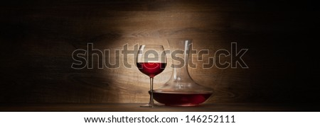 decanter with red wine and glass on a wood panorama background - stock photo