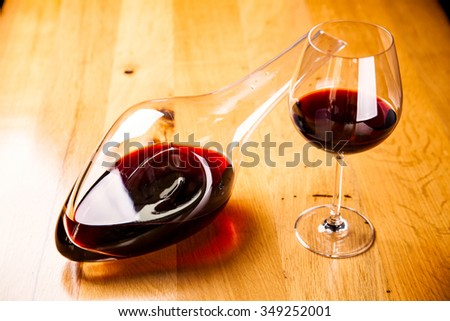 Decanter with red wine and glass on wooden table - stock photo