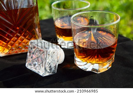 Decanter with two glasses of whiskey on a black table