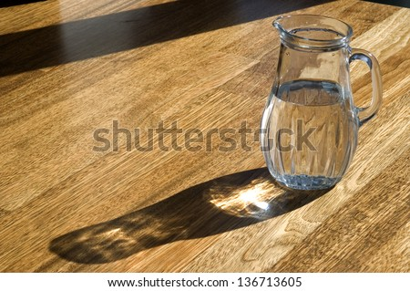 Decanter with water on a wooden floor. - stock photo