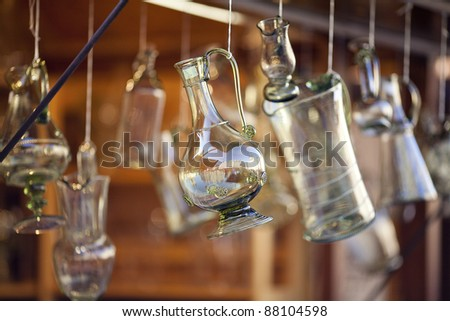 decanters of bohemian glass hanging on hooks - stock photo