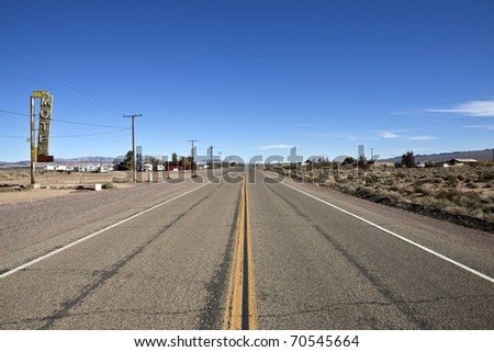 Decayed portion of historic Route 66 in the middle of California's vast Mojave desert. - stock photo