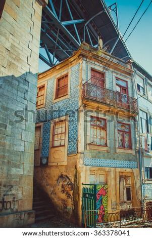 Decaying building in Porto under a bridge. - stock photo
