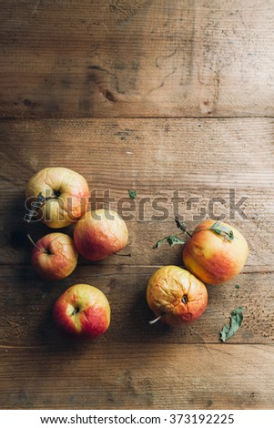Decaying organic apples on wooden table - stock photo
