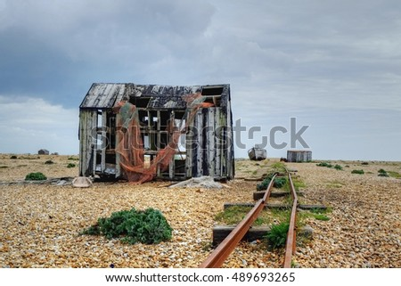 Decaying rail tracks and buildings on the shingle headland Dungeness on the Kent coast.