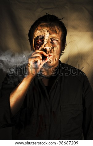 Decaying zombie smoking a cigarette in a conceptual image of what can happen to someone who cannot kick the habit - stock photo