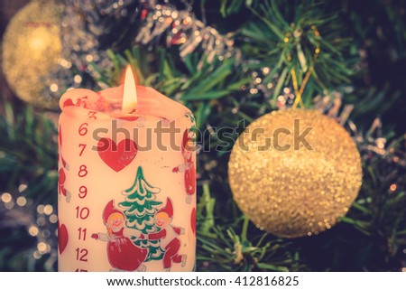 December calendar candle with shiny baubles and a Christmas tree - stock photo