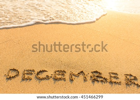 December - drawn by hand on a golden sandy sea beach. - stock photo
