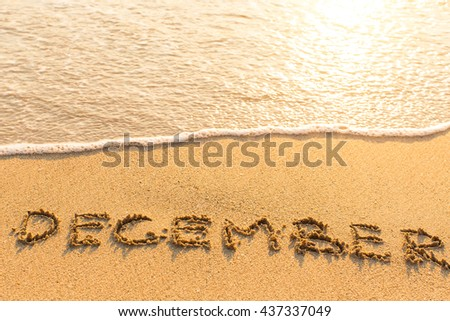 December - written on sandy beach with the soft wave. - stock photo