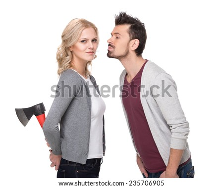 Deception. Conflict. Young couple, man wants to kiss his girlfriend and she is holding ax behind. White background.