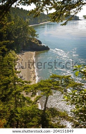 Deception Pass State Park, Washington. A lovely beach, called North Beach, attracts hundreds of visitors each day during the summer months. Great views of the bridge and old growth trees draw crowds. - stock photo