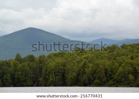 Decidious forest trees line the banks of Moosehead lake at the base of the mountains just before rain moves in - stock photo