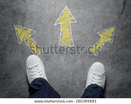 Decisions, high angle view of three arrows pointed in different directions drawn on the street - stock photo
