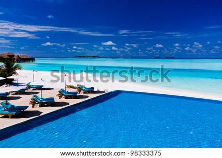 Deck and infinity pool over amazing tropical lagoon - stock photo