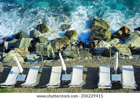 Deck chair at a rocky beach. Mediterranean sea, Italy - stock photo