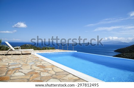 Deck chair on an infinity pool - stock photo