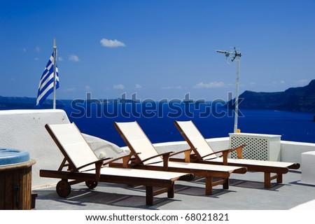 Deck chair on the terrace of a luxury villa in Santorini island, Greece - stock photo