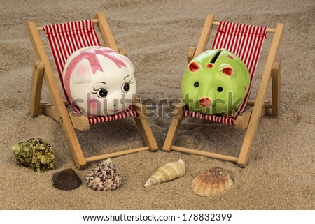 deck chair with piggy bank on the sandy beach. symbolic photo for travel costs, holidays, vacations. save on holiday - stock photo