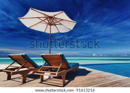 Deck chairs and infinity pool over amazing tropical lagoon - stock photo