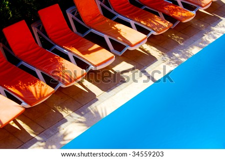 deck chairs and swimming pool - stock photo