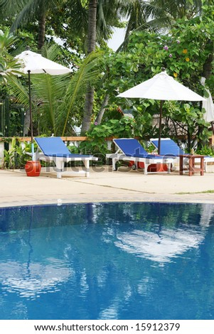 Deck chairs and umbrellas next to a swimming pool. - stock photo