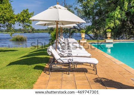 Deck Chairs around a beautiful swimming pool on a hot sunny day