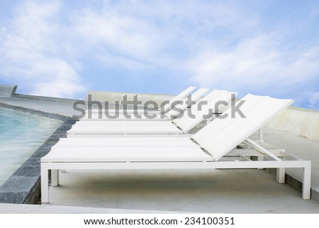 Deck chairs beside swimming pool on blue sky beach background. - stock photo