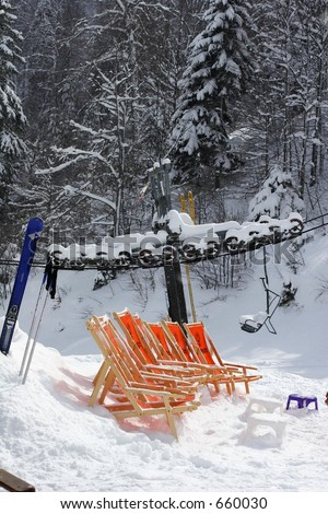 Deck chairs in the snow. - stock photo
