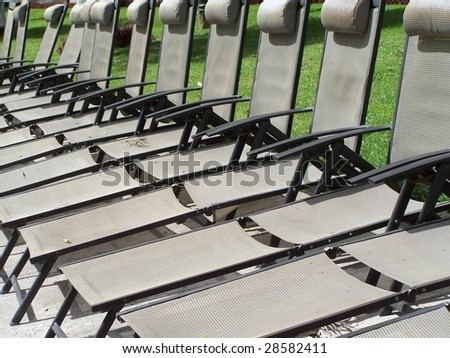 Deck chairs lined up at a resort - stock photo