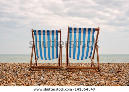 Deck chairs on the beach in Brighton  - stock photo