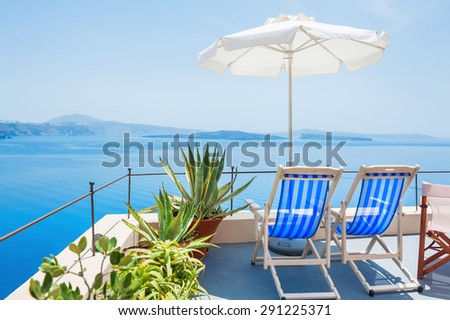 Deck chairs on the terrace with sea view. Santorini island, Greece. Beautiful summer landscape  - stock photo