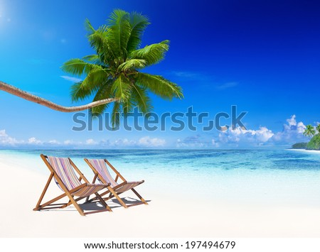 Deck chairs on tropical beach. - stock photo