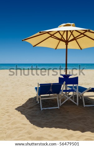 Deck chairs under an umbrella in the sand against the blue sea - stock photo