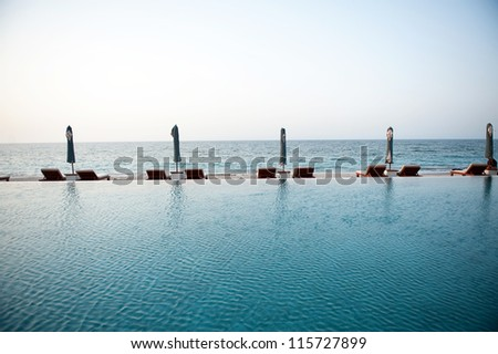 Deck chairs under sun umbrella between an infinity pool and the sea. - stock photo