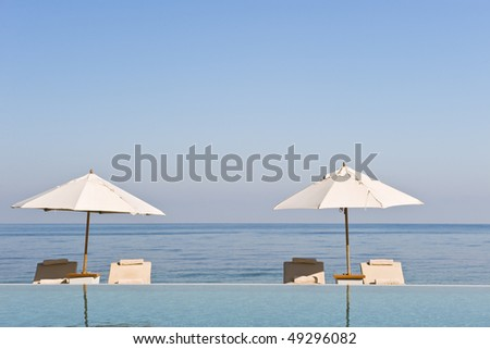 Deck chairs under sun umbrella between an infinity pool and the sea. Copy space provided on top. - stock photo