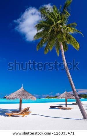 Deck chairs under umbrellas and palm trees in Maldives - stock photo