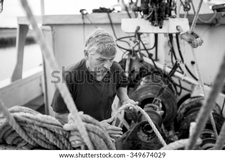 deck hand on fishing vessel doing hard work