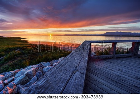 Deck, logs, and sunset. Perfect! - stock photo